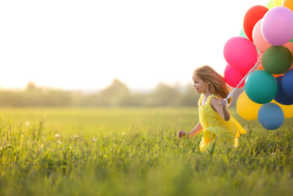 Mädchen mit Luftballons auf einer Wiese